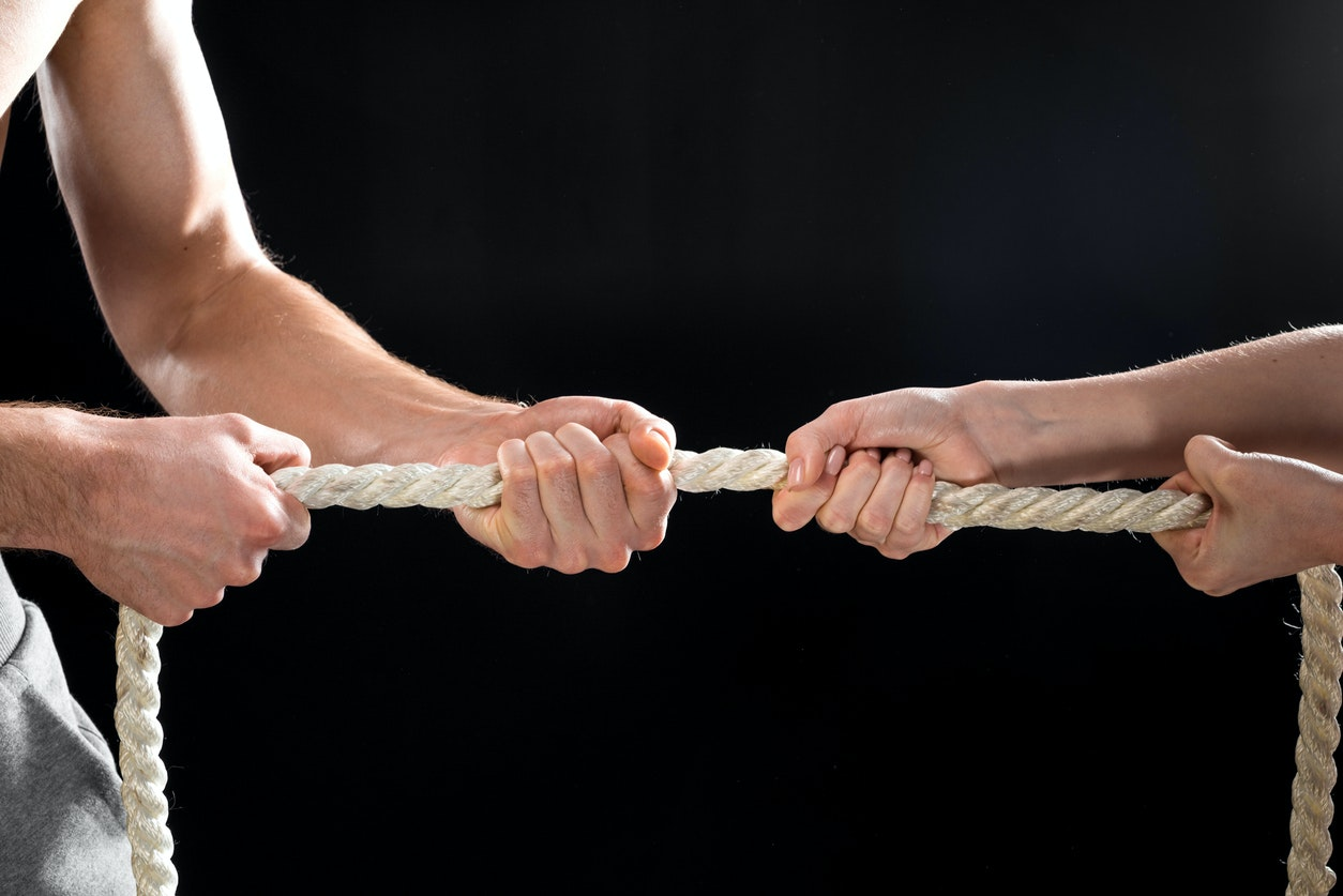 cropped view of man and woman pulling rope isolated on black