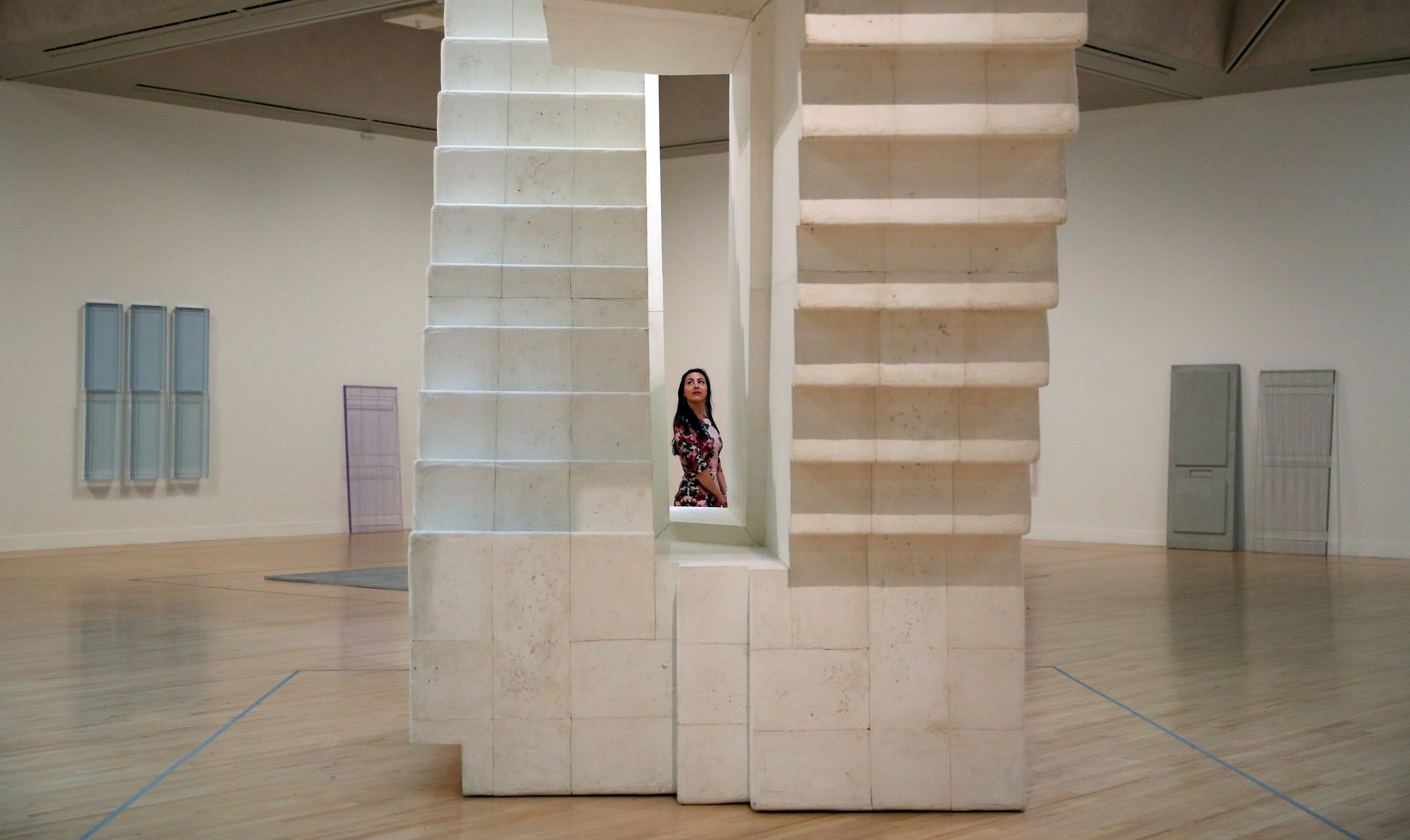 """A gallery assistant poses in front of Rachel Whiteread's installation """"Untitled (Stairs)"""" at the Tate Britain in London, Britain, September 11, 2017. REUTERS/Hannah McKay      FOR EDITORIAL USE ONLY. NOT FOR SALE FOR MARKETING OR ADVERTISING CAMPAIGNS - RC1CC11AC390"""